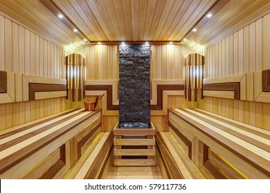 Inside in big Russian bath. Interior of wooden sauna in light and dark colors with bench, many little lamp on ceiling. Hot stones and bucket of water. Health care.