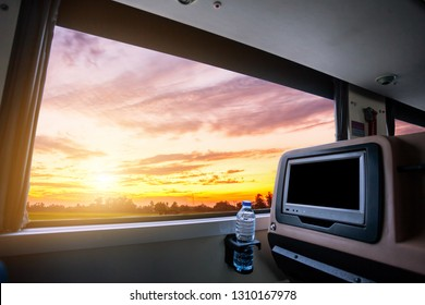 Inside of the bus which has LCD screen blank rear seat for entertainment with a bottle of water and window view of Beautiful landscape nature with sky cloud sunset, Figure tourism road trip concept.