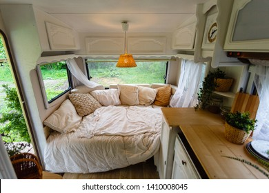 Inside the camper van. Unmade bed, pillows, white wooden interior decoration with lamp center. A cozy sleeping place for a young couple to sleep inside a camper for traveling.