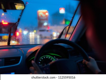 Inside a car driven by a woman under the rain by night.