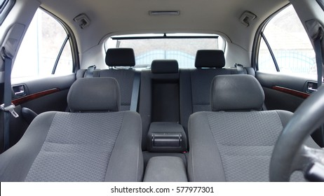 Inside car interior with front and back seats, driver and passenger, part from steering wheel, back curtain, fabric, textile, windows, door panels, central arm rest, console