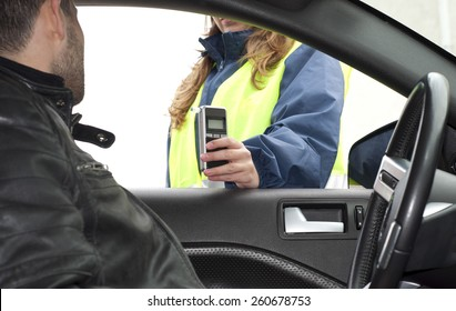 Inside the car view of a young drink and drive crashed driver due to being subject to test for alcohol content with use of breathalyzer
