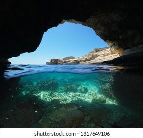 Inside a cave on the seashore, split view half over and under water, Mediterranean sea, Spain, Cabo de Gata Nijar natural park, Almeria, Andalusia