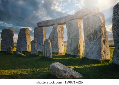 Inside the circle of stones at Stonehenge with the morning sun casting rays through the rock