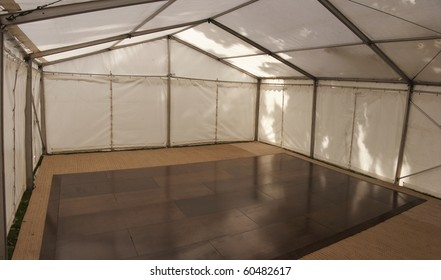 inside a clear span marquee (aluminum framework marquee) on a summer day
