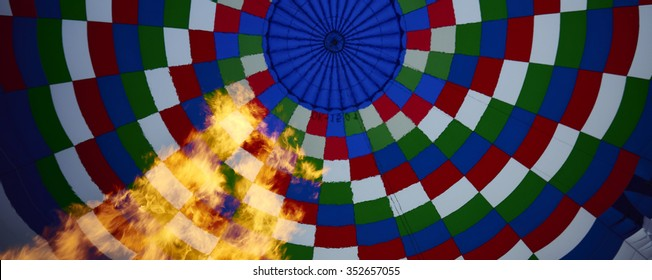 Inside of a colorful hot air balloon as it is inflated for flight, burning burner