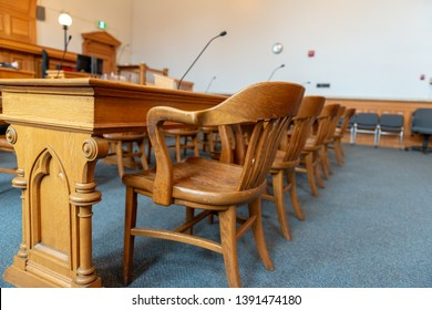 The inside of a court of law. The judge's bench, at the back of the courtroom is raised. The defendants table and chair, made of oak wood, is in the foreground. There are microphones on the table.