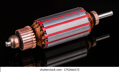 Inside of DC motor rotor with reflection on black background. Artistic still life of dismantled rotary electrical engine. Commutator, wire winding and transformer sheets on shaft. Full depth of field.