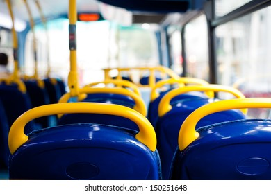 Inside a double decker bus empty seats. London, UK. Interior with yellow and blue chairs and seats.