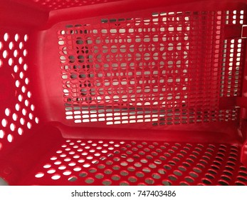 inside of an empty red shopping cart with lots of holes and no items