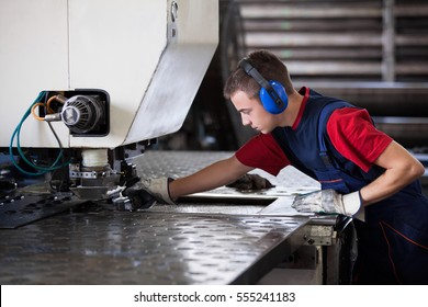 Inside a factory, industrial worker in action on metal press machine holding a steel piece ready to be worked.