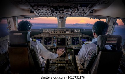 inside flight deck Commercial Pilots controlling the modern jet aircraft ,beautiful early morning view outside with Fuji Mountain view in Japan.