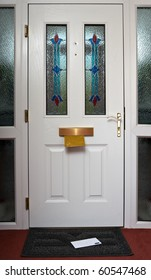 The inside of a front door with a letter in the in flap and on the doormat