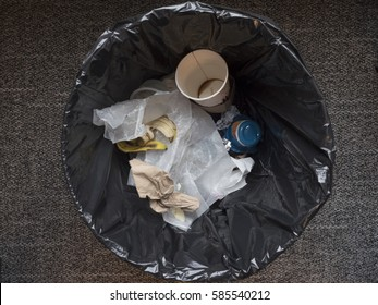 Inside of a garbage can with trash including empty coffee cup, wax paper, banana peel.  Plastic bag lining trash can