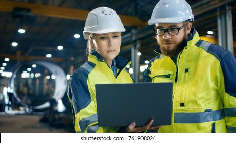 Inside the Heavy Industrial Factory Female Industrial Engineer Holds Laptop and Has Discussion with Project Manager. They Wear Hard Hats and Safety Jackets. In the Background Metalwork in Progress.