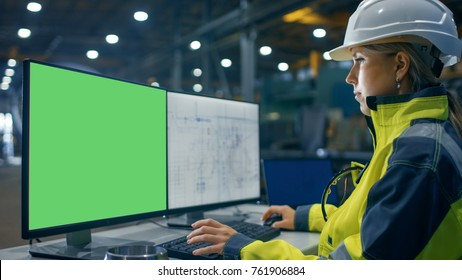Inside the Heavy Industry Factory Female Industrial Engineer Works on the Personal Computer with Green Mock-up Screen. Secondary Monitor Shows Blueprints.