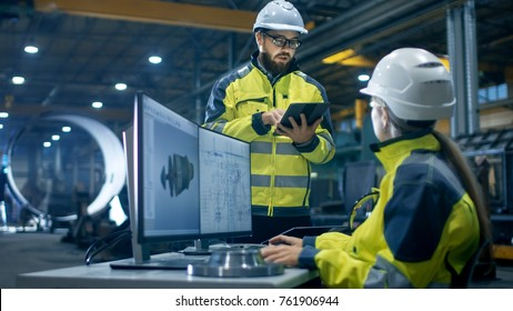 Inside the Heavy Industry Factory Female Industrial Engineer Works on Personal Computer She Designs 3D Turbine Model, Her Male Colleague Talks with Her and Uses Tablet Computer.