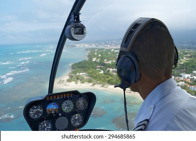 Inside Helicopter Pilot In Seat Over Tropical Landscape