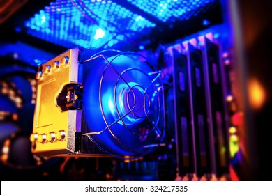 Inside a high performance computer. Computer circuit board and CPU cooling fans illuminated by internal LEDs inside a server class hardware.