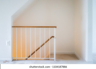 Inside house home interior, townhouse with stairs, steps or staircase leading down to basement level with yellow light lamp glowing, railing
