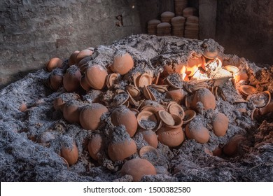 The inside of a kiln after firing with pots and dishes scattered among ashes from the firing process.