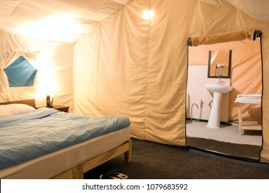 Inside a large white tent camp with bed at tourist camp in Pangong Tso, Ladakh, India.