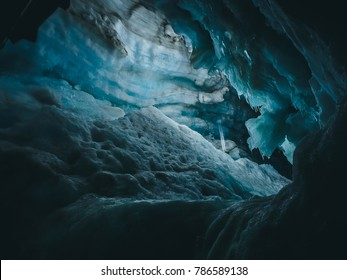 Inside the melting Langjokull glacier, Iceland. Blue ice with water falling from the ceiling of an ice cave. Horizontal