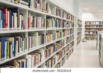 Inside a modern library with white book shelves and white wall