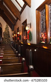 the inside of an old church with Christmas wreaths and candles, lights and a tree
