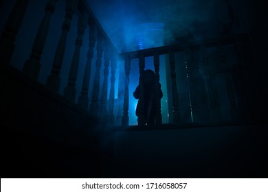 Inside of old creepy abandoned mansion. Silhouette of horror baby ghost standing on castle stairs to the basement. Horror Halloween concept