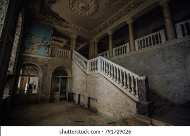 Inside of old creepy abandoned mansion. Staircase and colonnade.