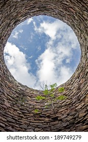 The inside of an old industrial chimney shaft photographed from the bottom - circular stone wall with tree growing from it and blue sky with white clouds in the opening in the centre, vertical
