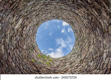 The inside of an old industrial chimney shaft photographed from the bottom - circular stone wall with tree growing from it and blue sky with white clouds in the opening in the center, horizontal