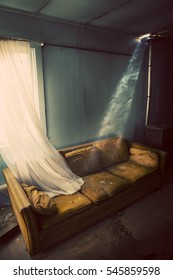 Inside old living room with broken glass and worn out couch.  Image is treated for a dated vintage feel.