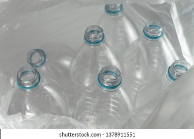 Inside an open transparent plastic bag with several empty bottles of liter and a half mineral water, without caps, just with the blue sealing ring. Reuse, Eco-Friendly, Environment, Conservation