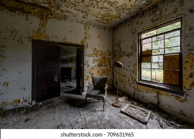 Inside a patient room with some furniture in a long abandoned hospital and nursing home.
