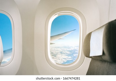 Inside of a plane window view of wing during flight of airplane interior with seat background.