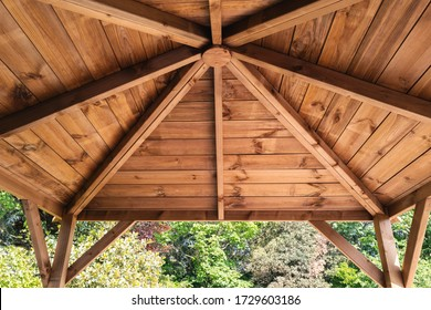 The inside roof of a wooden garden gazebo, looking up and out from within.