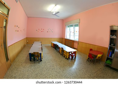 inside a school classroom of a nursery school without children but with many tables and chairs