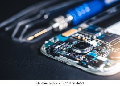 The inside of the smartphone's motherboard and tools lay on the back table. the concept of computer hardware, mobile phone, electronic, repairing, upgrade and technology.