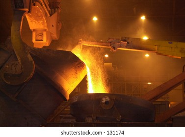 Inside of a steel mill, hot metal pouring.