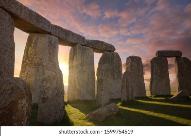 Inside the Stonehenge Circle of Stones with a Dramatic Sky Sunrise behind it
