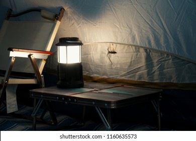 Inside tent camping at night. Lighting form LED lamp on the table. Camping and outdoor concept. Selective focus and free space for text.