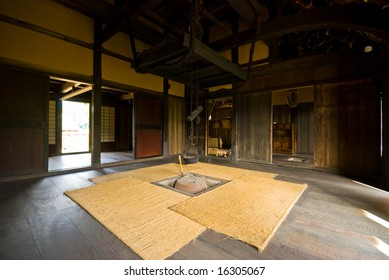 Inside of thatched farmhouse. hearth at the center of the room.