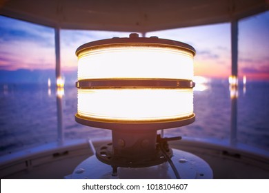 Inside the top of a lighthouse overlooking the sea with the ligh