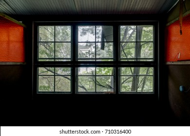 Inside a typical resort room that looks out large windows into the forest at an abandoned resort in the Catskill Mountains of New York.