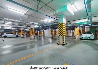 Inside view of bright and clean underground parking garage with cars in basement of high-rise apartment building. Rostov-on-Don, Russia - 15 oct 2020.