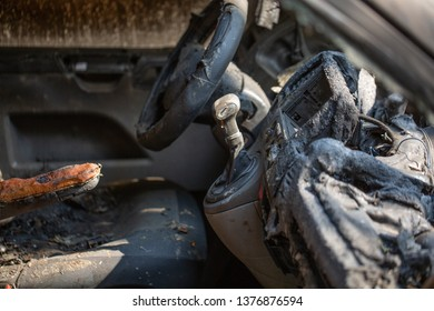 inside view of burnt out wreckage of a stolen car. Crime scene image of vehicle interior ruined by fire or arson. molten plastic and metal and steering wheel.