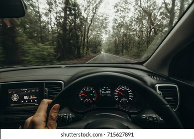 Inside view of car steering wheel while driving across Australian road