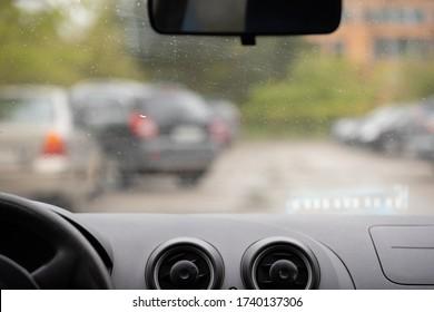 Vue intérieure de la voiture à travers le pare-brise de la rue. Panneau avant, volant, miroir au premier plan. Dehors de la fenêtre il pleut et beaucoup de voitures dans le parking.